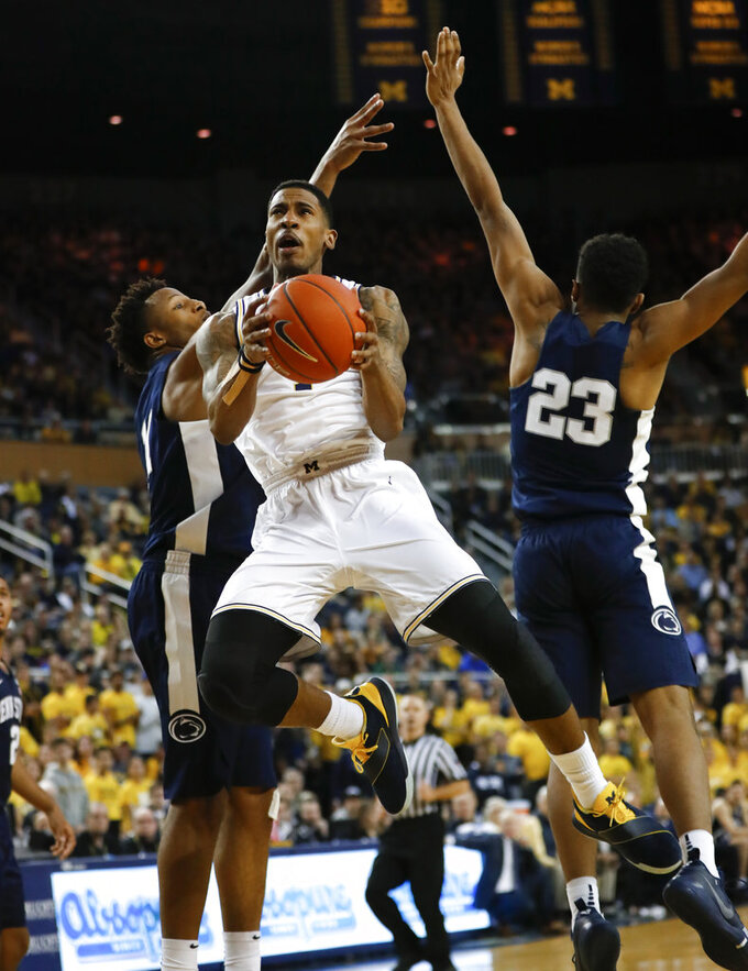Michigan guard Charles Matthews (1) drives against Penn State guard Josh Reaves (23) and another defender during the second half of an NCAA college basketball game in Ann Arbor, Mich., Thursday, Jan. 3, 2019. (AP Photo/Paul Sancya)