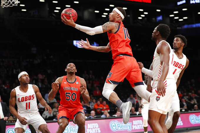 New Mexico guard JJ Caldwell (11) and Auburn center Austin Wiley (50) watch from the floor as Auburn guard Samir Doughty (10) goes up for two points during the second half of an NCAA college basketball game against New Mexico in the Legends Classic, Monday, Nov. 25, 2019, in New York. Auburn defeated New Mexico 84-59. (AP Photo/Kathy Willens)