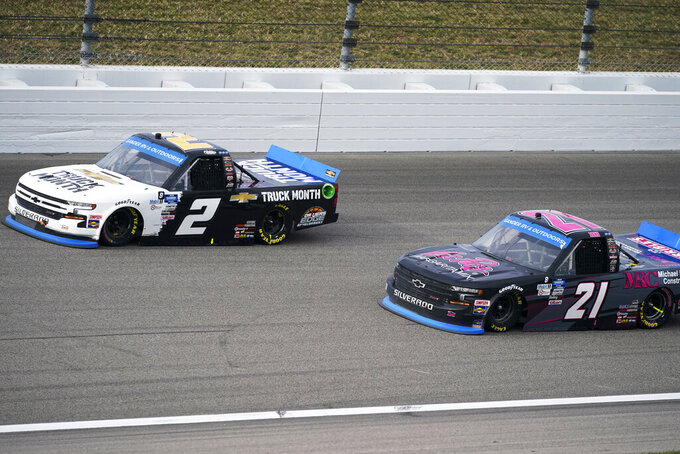 Zane Smith (21) passes Sheldon Creed (2) on the inside during a NASCAR Truck Series auto race at Kansas Speedway in Kansas City, Kan., Saturday, Oct. 17, 2020. (AP Photo/Orlin Wagner)