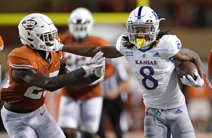 Kansas' Kwamie Lassiter II (8) tries to run past Texas' B.J. Foster (25) during the second half of an NCAA college football game in Austin, Texas, Saturday, Oct. 19, 2019. (AP Photo/Chuck Burton)