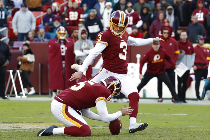 Washington Redskins kicker Dustin Hopkins (3) hits a field goal against the Philadelphia Eagles in the second half of an NFL football game, Sunday, Dec. 15, 2019, in Landover, Md. Holding the ball is Washington Redskins punter Tress Way (5). (AP Photo/Alex Brandon)