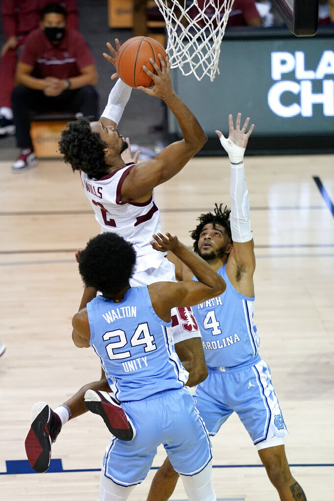 Stanford guard Bryce Wills (2) leaps to the basket over North Carolina guards Kerwin Walton (24) and R.J. Davis (4) during the second half of an NCAA college basketball game in the semifinals of the Maui Invitational, Tuesday, Dec.1, 2020, in Asheville, N.C. (AP Photo/Kathy Kmonicek)