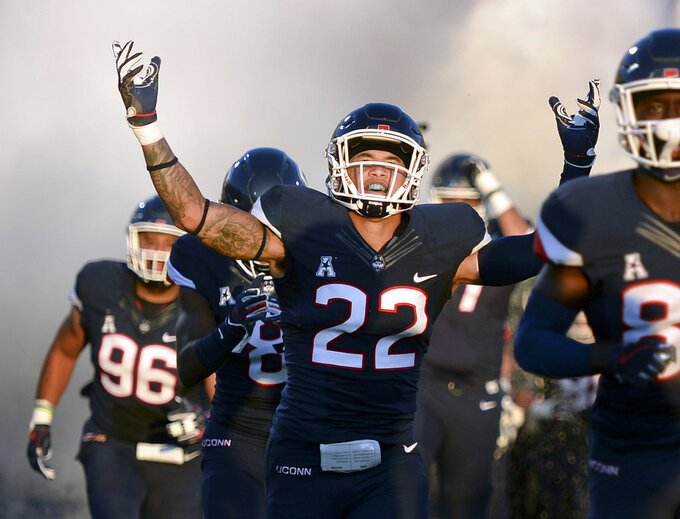 FILE - In this Aug. 30, 2018 file photo, Connecticut linebacker Eli Thomas (22) raises his arms to the crowd as his team enters the field for their season-opening NCAA college football game against Central Florida in East Hartford, Conn. UConn issued a statement Monday, Oct. 15, saying Thomas, a 220-pound junior, was hospitalized after suffering a stroke the preceding Wednesday prior to a weightlifting session. (AP Photo/Stephen Dunn, File)