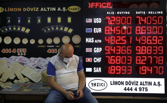 A man sits outside an exchange office in Istanbul, Friday, Aug. 7, 2020. Turkey's currency tumbled further Friday, hitting another record low. The Turkish lira dropped to 7.3677 against the dollar before making a recovery. The lira is down about 19% versus the U.S. currency since the beginning of the year. (AP Photo/Emrah Gurel)