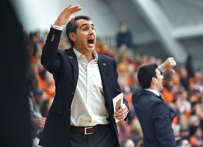 Colgate coach Matt Langel, left, yells instructions to his players during the first half of an NCAA college basketball game against Bucknell for the championship of the Patriot League men's tournament in Hamilton, N.Y., Wednesday, March 13, 2019. (AP Photo/Adrian Kraus)