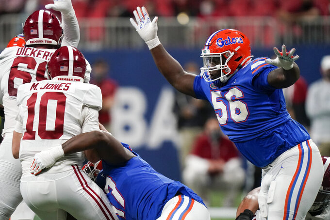 Florida defensive lineman Zachary Carter (17) hits Alabama quarterback Mac Jones (10) as Florida defensive lineman Tedarrell Slaton (56) rushes during the first half of the Southeastern Conference championship NCAA college football game, Saturday, Dec. 19, 2020, in Atlanta. (AP Photo/Brynn Anderson)