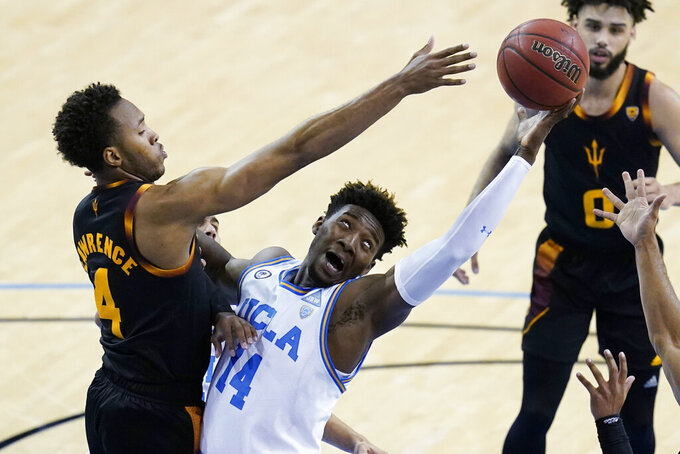 Arizona State forward Kimani Lawrence (4) and UCLA forward Kenneth Nwuba (14) reach for a rebound during the second half of an NCAA college basketball game Saturday, Feb. 20, 2021, in Los Angeles. (AP Photo/Ashley Landis)
