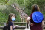 Izzy Brown Moore, 8, of Arlington, Mass., left, wears a mask out of concern for the coronavirus while visiting a giraffe exhibit with her grandmother Fran Brown, of Newton, Mass., right, at the Franklin Park Zoo, Thursday, May 28, 2020, in Boston. The zoo was open to members only Thursday for the first time in about two months due to concerns about COVID-19. Safety measures such as one way paths and safe distancing have been implemented at the zoo. The zoo is to open to the general public starting June 4. (AP Photo/Steven Senne)