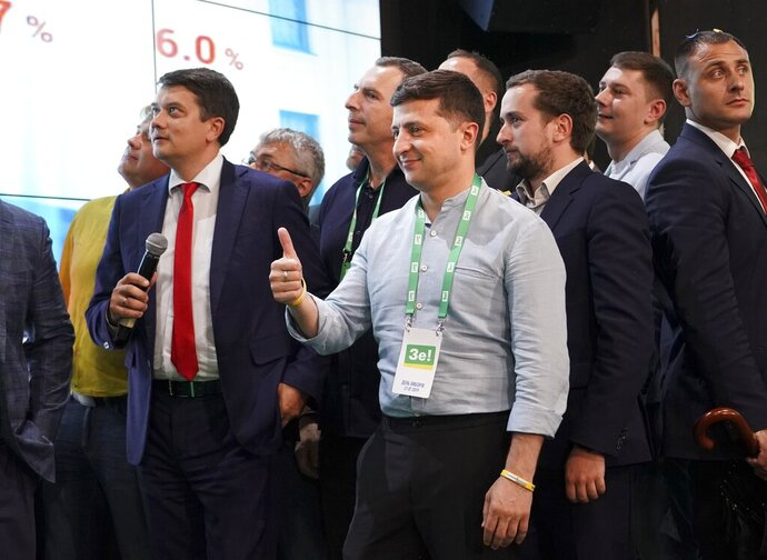 Ukrainian President Volodymyr Zelenskiy, center, reacts with his team as they look at the election results at his party's headquarters after a parliamentary election in Kiev, Ukraine, Sunday, July 21, 2019. Zelenskiy's party took the largest share of votes in the country's snap parliamentary election, an exit poll showed Sunday. (AP Photo/Evgeniy Maloletka)