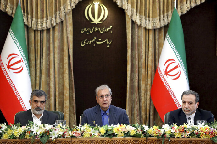 From left to right, spokesman for Iran's atomic agency Behrouz Kamalvandi, Iran's government spokesman Ali Rabiei and Iranian Deputy Foreign Minister Abbas Araghchi, attend a meeting in Tehran, Iran, Sunday, July 7, 2019. The deputy foreign minister says that his nation considers the 2015 nuclear deal with world powers to be a