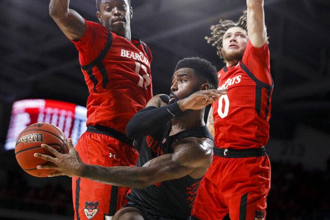 Houston's Corey Davis Jr., center, passes against Cincinnati's Tre Scott, left, and Logan Johnson (0) in the second half of an NCAA college basketball game, Sunday, March 10, 2019, in Cincinnati. (AP Photo/John Minchillo)
