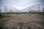 A roller coaster stands tall in the abandoned amusement park coined