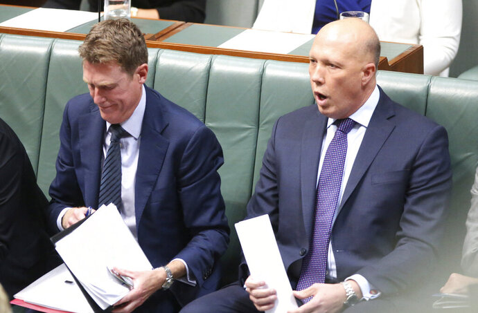 Home Affairs Minister Peter Dutton, right, listens to debate in Parliament House in Canberra, Australia, on Tuesday, Feb. 25, 2020. Dutton says China is not solely to blame for the foreign interference that a spymaster reports has reached unprecedented levels in Australia. (AP Photo/Rod McGuirk)