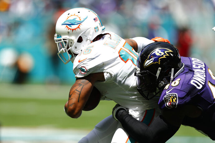 """FILE - In this Sept. 8, 2019, file photo, Miami Dolphins wide receiver Albert Wilson (15) is tackled by Baltimore Ravens inside linebacker Patrick Onwuasor (48), during the first half at an NFL football game in Miami Gardens, Fla. The new man in the middle of the Ravens defense is Patrick Onwuasor, who arrived in the NFL as an undrafted free agent and carries the not-so-fearsome nickname """"Peanut."""" Playing the position formerly held by Ray Lewis and C.J. Mosley, Onwuasor wore the headset anointed to the leader of the defense and performed precisely as expected in the opener against Miami last Sunday. He led the Ravens with five tackles, had one of the team's three sacks and keyed a unit that allowed just 21 yards rushing in a 59-10 victory.(AP Photo/Brynn Anderson, File)"""