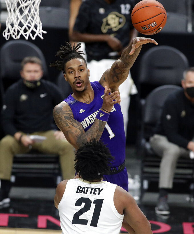 Washington's Nate Roberts (1) passes as Colorado's Evan Battey (21) defends during the first half of an NCAA college basketball game, Sunday, Dec. 20, 2020, in Las Vegas. (AP Photo/Isaac Brekken)