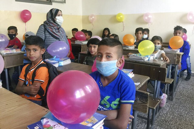 In this photo released by the Syrian official news agency SANA, students attend a lesson on their first day back at school, in Qamishli, Syria, Sunday, Sept. 13, 2020. More than 3 million students went to school in government-held areas around Syria Sunday marking the first school day amid strict measures to prevent the spread of coronavirus. (SANA via AP)