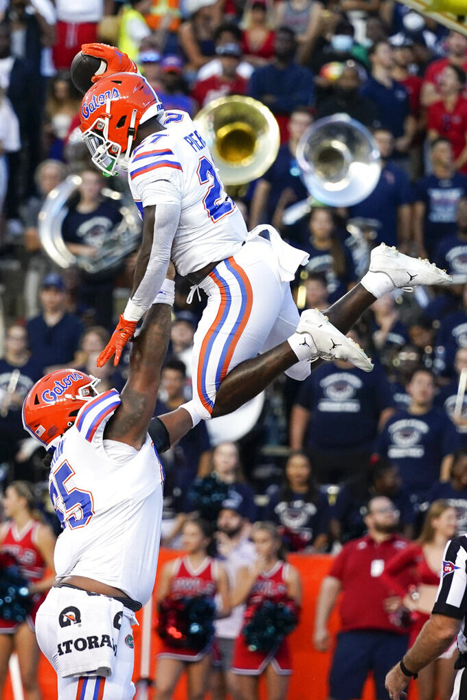 Florida running back Dameon Pierce is lifted by offensive lineman Kingsley Eguakun after scoring a touchdown against Florida Atlantic during the first half of an NCAA college football game Saturday, Sept. 4, 2021, in Gainesville, Fla. (AP Photo/John Raoux)
