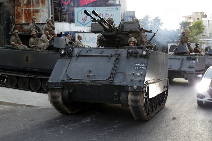 Lebanese army soldiers sit on their armored vehicles as they deployed to contain the tension after heavy fire in the coastal town of Khaldeh, south of Beirut, Lebanon, Sunday, Aug. 1, 2021. At least two people were killed on Sunday south of the Lebanese capital when gunmen opened fire at the funeral of a Hezbollah commander who was killed a day earlier, an official from the group said. (AP Photo/Bilal Hussein)