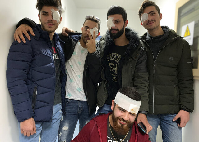 In this Jan. 27, 2020 photo, anti-government protesters, who were injured during clashing with riot police, pose for a group picture after a check up with an ophthalmologist at a hospital in Beirut, Lebanon. The five pledged that they'll be back in the streets soon. Such resolve signals that demands for sweeping government reforms won't be squashed easily, even as security forces resort to more violent means of crowd control, such as rubber bullets. (AP Photo/A.J. Naddaff)