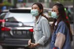 People wear face masks as a precaution against the new coronavirus on a street in Jakarta, Indonesia Monday, June 8, 2020. Indonesia's capital of Jakarta, the city hardest hit by the new coronavirus, has partly reopened after two months of partial lockdown as the world's fourth most populous nation braces to gradually reopen its economy. (AP Photo/Achmad Ibrahim)