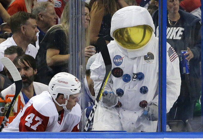 FILE - In this April 13, 2016, file photo, a Tampa Bay Lightning fan wearing an astronaut suit taunts Detroit Red Wings defenseman Alexei Marchenko (47), of Russia, during the third period of Game 1 in a first-round NHL hockey Stanley Cup playoff series in Tampa, Fla. The roar of the crowd has been a staple of major sports. Playing in empty buildings would require a significant recalibration. (AP Photo/Chris O'Meara, File)