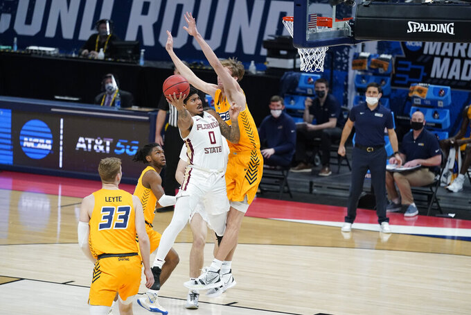 Florida State's RayQuan Evans (0) puts up a shot against UNC-Greensboro's Hayden Koval (25) during the first half of a first-round game in the NCAA men's college basketball tournament at Banker's Life Fieldhouse, Saturday, March 20, 2021, in Indianapolis. (AP Photo/Darron Cummings)