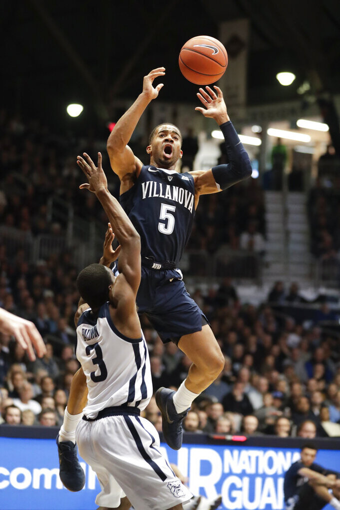 Villanova guard Phil Booth (5) is fouled as he shoots by Butler guard Kamar Baldwin (3) in the first half of an NCAA college basketball game in Indianapolis, Tuesday, Jan. 22, 2019. (AP Photo/Michael Conroy)