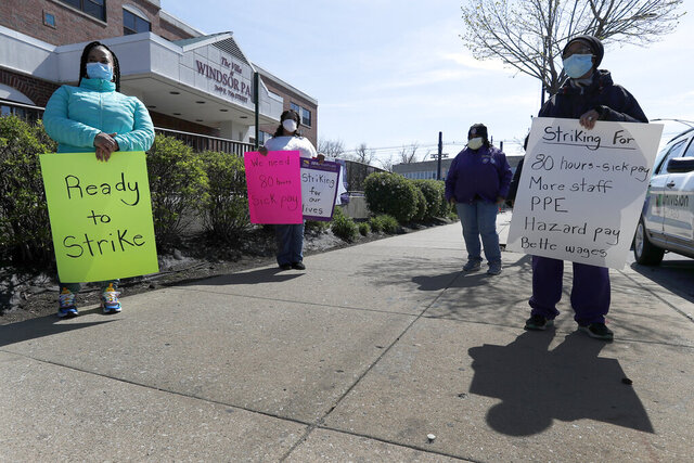 Certified nurse's assistants stand during an informational picket outside The Villa at Windsor Park nursing home on Chicago's Southside on Wednesday, May 6, 2020. Staff at dozens of Illinois nursing homes called off a strike set to begin Friday after the workers' union reached a tentative deal with nursing home owners that union officials said would help safeguard both staff and residents during the coronavirus pandemic. (AP Photo/Charles Rex Arbogast)