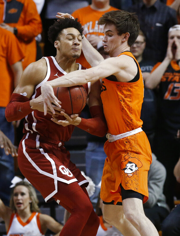 Oklahoma State forward Duncan Demuth, right, reaches for the ball held by Oklahoma center Jamuni McNeace during the first half of an NCAA college basketball game in Stillwater, Okla., Wednesday, Jan. 23, 2019. (AP Photo/Sue Ogrocki)