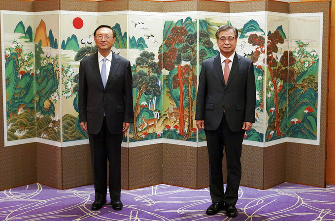 Yang Jiechi, left, a top Chinese official in charge of diplomatic affairs, and South Korean National Security Council Chairman Suh Hoon pose for photos during a meeting at a hotel in Busan, South Korea, Saturday, Aug. 22, 2020. (Lee Jin-wook/Yonhap via AP)