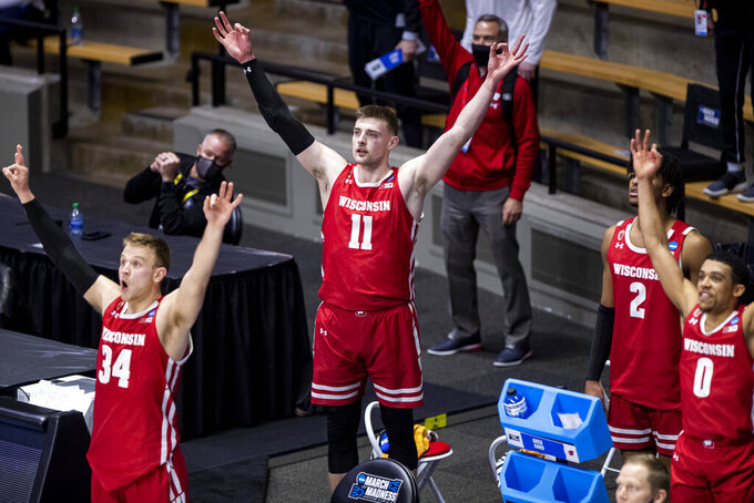 Wisconsin's Brad Davison (34), Micah Potter (11), Aleem Ford (2) and D'Mitrik Trice (0) celebrate a late three-point basket in the first-round game against North Carolina in the NCAA men's college basketball tournament, Friday, March 19, 2021, at Mackey Arena in West Lafayette, Ind. (AP Photo/Robert Franklin)