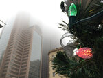 FILE - In this Dec. 19, 2018, file photo Christmas lights blink in the Main Street Garden Park as the Comerica Bank Tower disappears in a thick fog in downtown Dallas. Holiday staffing is one of a small business owner's biggest stressors. Even companies that aren't retailers or restaurants can have a year-end busy season, just when employees all want to take time off. (Irwin Thompson/The Dallas Morning News via AP, File)