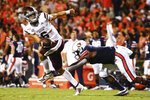 Mississippi State quarterback Garrett Shrader (6) escapes the pressure from Auburn defensive end Big Kat Bryant (1) during the first half of an NCAA college football game, Saturday, Sept. 28, 2019, in Auburn, Ala. (AP Photo/Butch Dill)