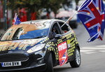 A man waves an EU and Union flag out of a car adorned with anti-Brexit decals in front of EU headquarters in Brussels, Thursday, Oct. 17, 2019. The European Union says Brexit negotiations are plowing on after intense talks in recent days, as EU leaders converge on Brussels for a key summit aimed at sealing a new divorce agreement. (AP Photo/Frank Augstein)