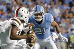 FILE - In this Sept. 7, 2019, file photo, Miami quarterback Jarren Williams (15) is pressured by North Carolina's Chazz Surratt (21) during the first half of an NCAA college football game in Chapel Hill, N.C. Chazz Surratt was selected to The Associated Press All-Atlantic Coast Conference football team, Tuesday, Dec. 10, 2019. (AP Photo/Chris Seward, File)