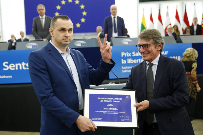 Ukrainian filmmaker Oleg Sentsov flashes the V sign as he gets his prize from European Parliament president David Sassoli, Tuesday Nov. 26, 2019 in Strasbourg, eastern France. A year after he won Europe's top human rights award, Oleg Sentsov finally picked up the prize, following his release from a prison in Russia's far-north where he was held on terror charges. (AP Photo/Jean-Francois Badias)