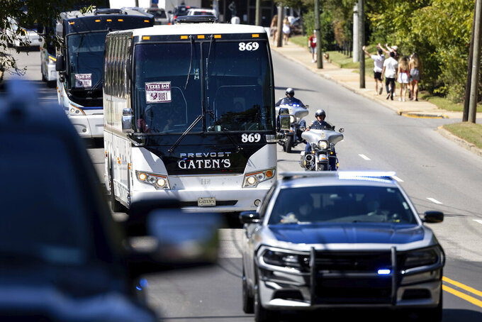 Texas A&M's caravan of buses arrives with a police escort for the team's NCAA college football game against Alabama on Saturday, Oct. 3, 2020, in Tuscaloosa, Ala. Only 20,000 fans were allowed to attend, meaning many did not travel to the city, while others sought social opportunities at restaurants and bars. (AP Photo/Vasha Hunt)