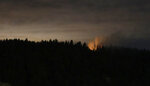 File - In this Aug. 11, 2018 file photo and long-exposure photo, smoke and an orange glow from a stolen airplane that crashed are seen on Ketron Island in Washington state, as viewed from near Steilacoom, Wash. Authorities say the Seattle airport ground crew worker who stole an empty commercial airplane had apparently searched online for flight instruction videos before he took off on a dizzying ride that soon crashed into a small island. The FBI announced Friday, Nov. 9, 2018, that it's concluding the investigation into the August 10 incident after determining that Richard Russell, 28, of Sumner, Washington, acted alone from Seattle-Tacoma International Airport. (AP Photo/Ted S. Warren, File)