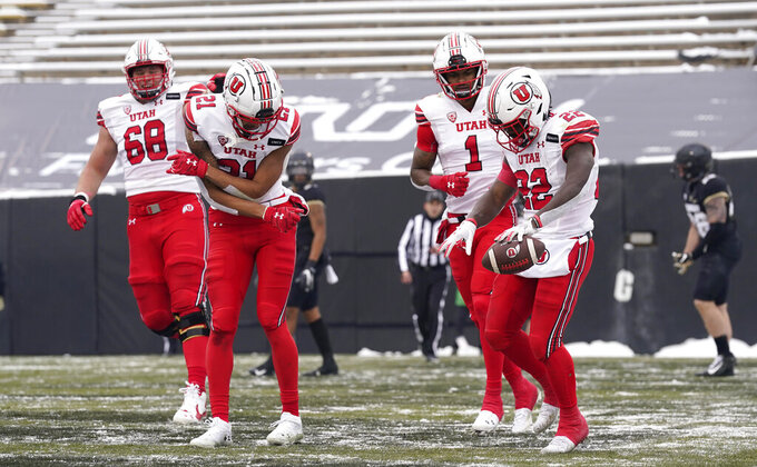 Utah running back Ty Jordan, right, celebrates after his touchdown run with, from left, offensive lineman Jaren Kump and wide receivers Solomon Enis and Bryan Thompson in the second half of an NCAA college football game against Colorado, Saturday, Dec. 12, 2020, in Boulder, Colo. Utah won 38-21. (AP Photo/David Zalubowski)