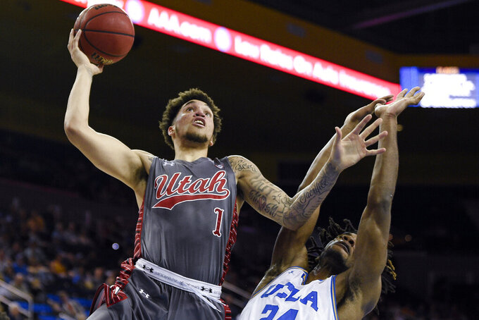 Utah forward Timmy Allen, left, goes up to shoot while UCLA forward Jalen Hill defends during the second half of an NCAA college basketball game in Los Angeles, Sunday, Feb. 2, 2020. (AP Photo/Kelvin Kuo)
