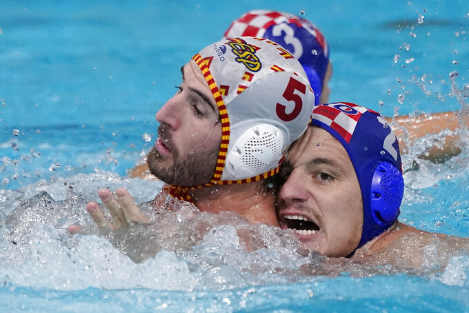 Spain's Miguel de Toro Dominguez (5) and Croatia's Marko Macan (2) battle for position during a preliminary round men's water polo match at the 2020 Summer Olympics, Monday, Aug. 2, 2021, in Tokyo, Japan. (AP Photo/Mark Humphrey)
