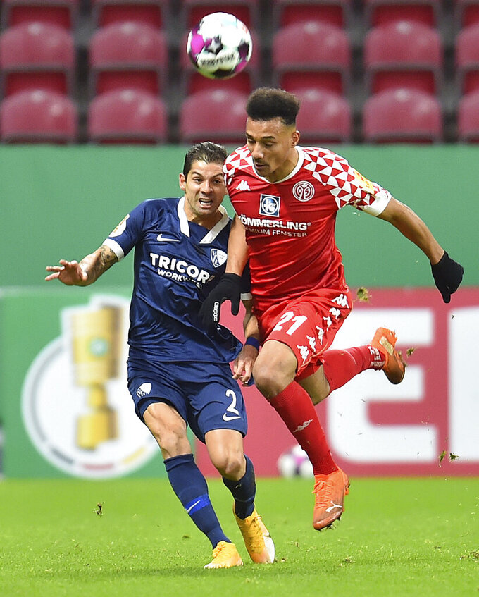Mainz's Karim Onisiwo, right, competes for the ball with Bochum's Cristian Gamboa, during the German Cup 2nd round soccer match between FSV Mainz 05 and VfL Bochum at the Opel Arena, in Mainz, Germany, Wednesday, Dec. 23, 2020. (Torsten Silz/dpa via AP)