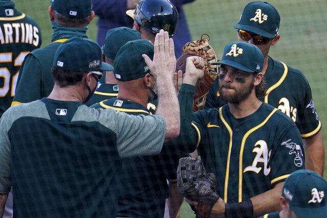 Oakland Athletics' Chad Pinder, right, celebrates with manager Bob Melvin after the Athletics defeated the Houston Astros in Game 3 of a baseball American League Division Series in Los Angeles, Wednesday, Oct. 7, 2020. (AP Photo/Marcio Jose Sanchez)