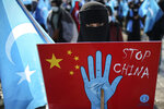 A protester from the Uyghur community living in Turkey holds up an anti-China placard during a protest against the visit of China's Foreign Minister Wang Yi to Turkey, in Istanbul, Thursday, March 25, 2021. Hundreds protested against the Chinese official visit and what they allege is oppression by the Chinese government to Muslim Uyghurs in the far-western Xinjiang province. (AP Photo/Emrah Gurel)