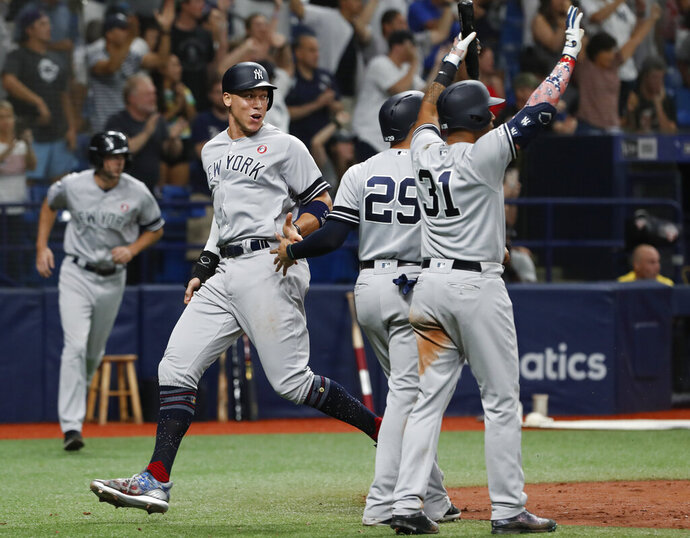 New York Yankees' Aaron Judge, left, celebrates with teammates after scoring during the 10th inning of a baseball game against the Tampa Bay Rays on Thursday, July 4, 2019, in St. Petersburg, Fla. (AP Photo/Scott Audette)