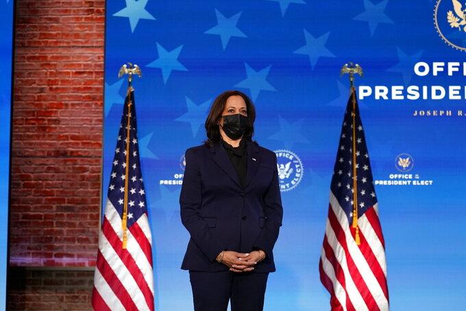Vice President-elect Kamala Harris listens as President-elect Joe Biden speaks during an event at The Queen theater, Friday, Jan. 15, 2021, in Wilmington, Del. (AP Photo/Matt Slocum)