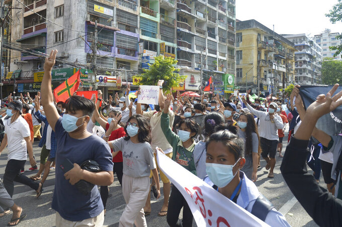 Anti-coup protesters flash the three-finger salute of defiance during a demonstration on Thursday, May 6, 2021, in Yangon, Myanmar. More than 200 global organizations urged the U.N. Security Council on Wednesday, May 5, 2021, to impose an arms embargo on Myanmar, saying the time for statements has passed and immediate action is needed to help protect peaceful protesters against military rule and other opponents of the junta. (AP Photo)