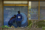 In this Jan. 9, 2020 photo, clients wait to enter the DirecTV headquarters in Caracas, Venezuela. Venezuelan President Maduro's opponents want AT&T's DirecTV unit to restore a number of channels it was required to take down from its lineup. But forcing AT&T to do the political bidding of Maduro's foes could lead to retaliation and likely exit from a market where it has a whopping 44% market share. (AP Photo/Matias Delacroix)