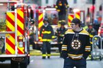 A Boston Bruins fan heads to an NHL hockey game between the Bruins and the Ottawa Senators at TD Garden while firefighters battle a three-alarm blaze in an adjacent building under construction in Boston, Saturday, March 9, 2019. (AP Photo/Michael Dwyer)