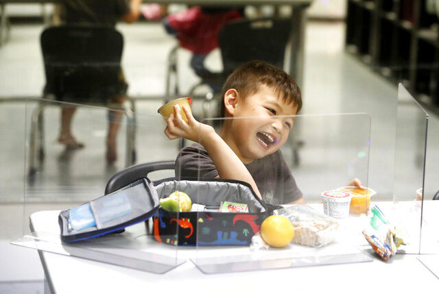 Bruce McCall, 5, laughs as he eats his lunch behind plastic barriers during martial arts daycare summer camp at Legendary Blackbelt Academy in Richardson, Texas, Tuesday, May 19, 2020. As daycare and youth camps re-open in Texas, operators are following appropriate safety measure to insure kids stay safe from COVID-19. (AP Photo/LM Otero)